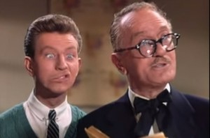 Bobby Watson in Singin' in the Rain, with onald O'Connor mugging behind him.