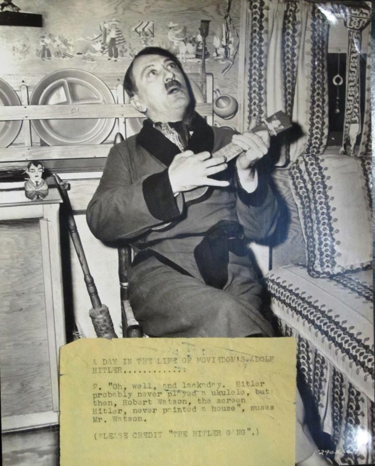 Watson plays a ukulele in his trailer during filming of The Hitler Gang (1944). Unlike most of the movies in which Watson played Hitler, The Hitler Gang was a straightforward history of the dictator's rise to power.