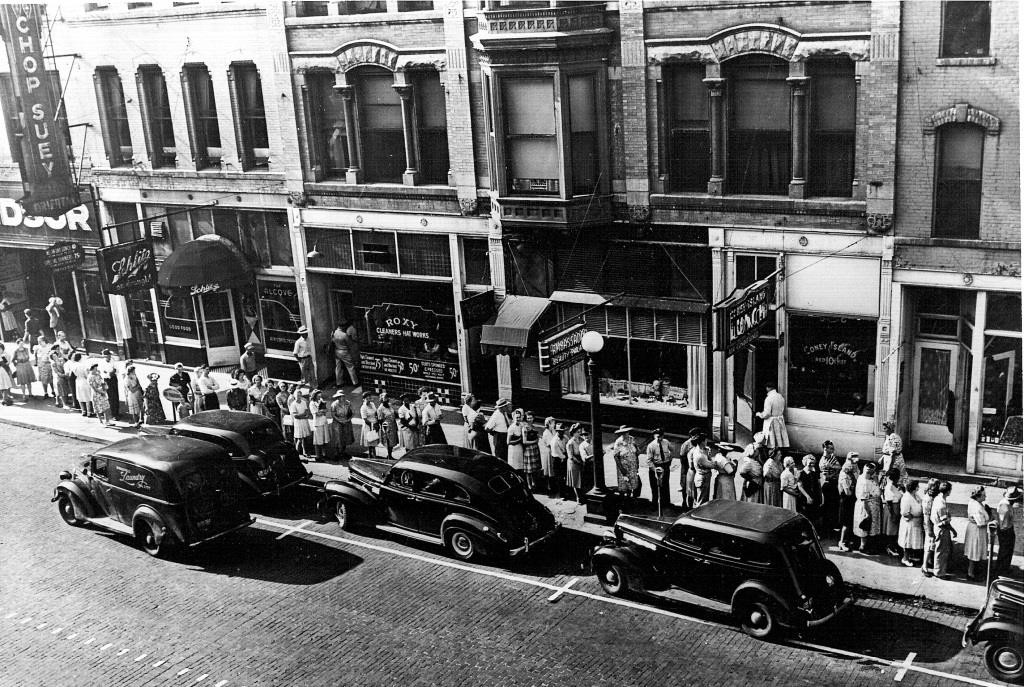 "The Oriental Cafe's ""Chop Suey"" sign can be seen at far left above the 400 block of East Monroe Street in 1943. (The line of pedestrians is queued up to redeem meet ration coupons at the Monroe Street Market, which is beyond the west edge of the photo. (Sangamon Valley Collection)"