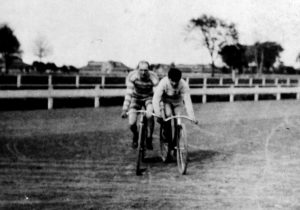 "Alfred J. Mester, left, of the Capital City Cycling Club in a ""safety bicycle"" race at the Illinois State Fairgrounds about 1900 (Sangamon Valley Collection)"