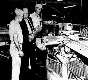 Bakery general manager George Cassem holds a loaf of bread at the bakery, 1971. Baker Fred Gillmore, left; production manager Robert Janzen, right. (Courtesy SJR files)