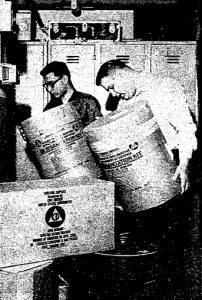 Dave Roscetti, left, and Bill Marsh stack sanitation kits (cardboard drums that served as toilets) during the 1964 State Office Building drill. (Courtesy SJ-R)